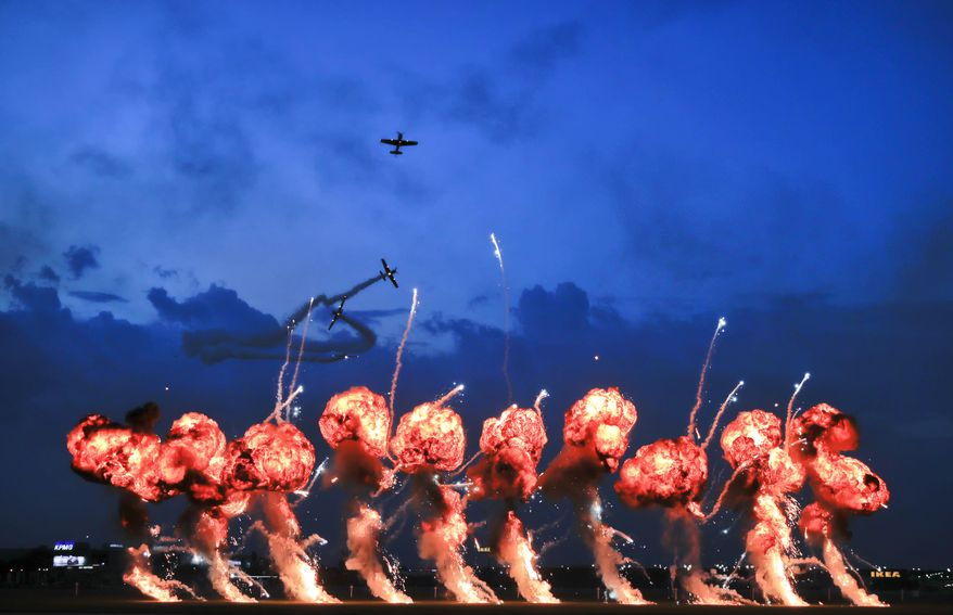In this Saturday, July 28, 2018, members of the Hawks of Romania aerobatics team fly as pyrotechnic effects are deployed to simulate a bombing raid, during the Bucharest International Air Show, or BIAS 2018, in Bucharest, Romania. Thousands of Romanians took to an airfield on the edge of the capital Bucharest for a weekend of aerobatics and air power display by more than 200 pilots and 150 aircraft from several countries.(AP Photo/Vadim Ghirda)