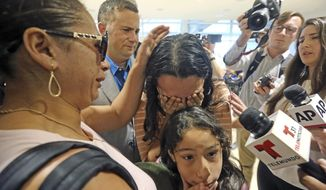 Alejandra Juarez,38, left, says goodbye to her children, Pamela and  Estela at the Orlando International Airport on Friday, Aug. 3, 2018 in Orlando, Fla.  Juarez, the wife of a former Marine is preparing to self-deport to Mexico in a move that would split up their family.  (Red Huber/Orlando Sentinel via AP)