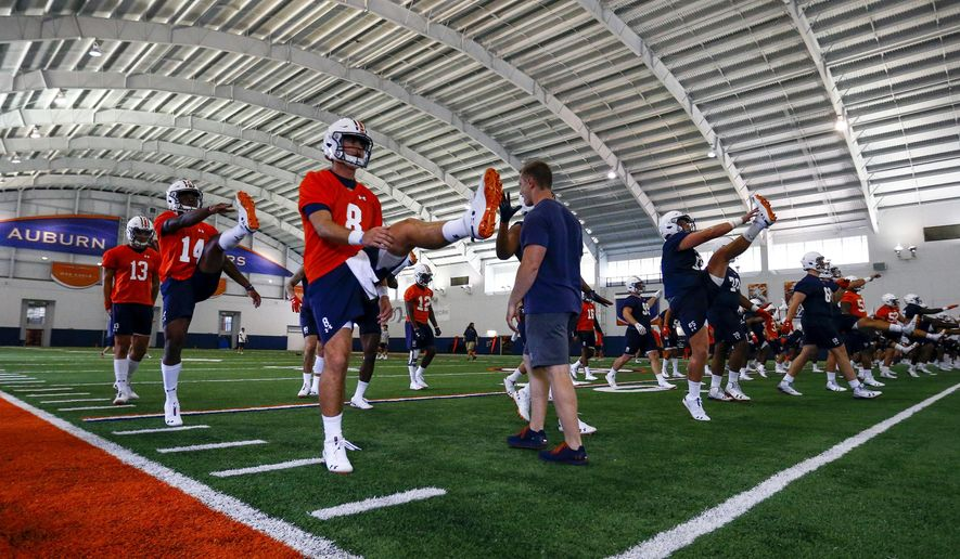 Auburn quarterback Jarrett Stidham (8) stretches with fellow players during NCAA college football practice, Friday, Aug. 3, 2018, in Auburn, Ala. (AP Photo/Butch Dill)