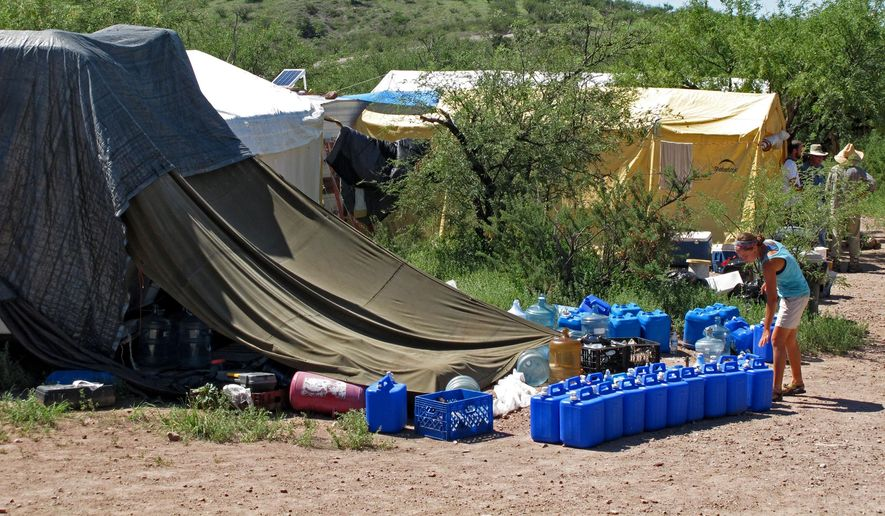 In this Thursday, Aug. 5, 2010, file photo, No More Deaths volunteer Katie Maloney checks water jugs at the group's camp before heading out to supply water stations for illegal immigrants near Arivaca, Ariz., about 13 miles north of Mexico. (AP Photo/Amanda Lee Myers, File)