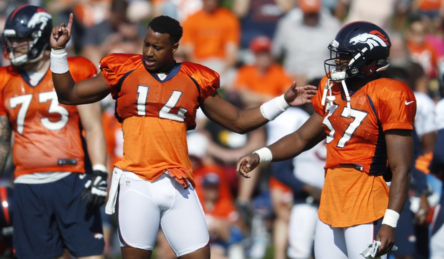 Denver Broncos wide receiver Courtland Sutton, left, jokes with running back Royce Freeman during a break in drills at the team's NFL football training camp Monday, July 30, 2018, in Englewood, Colo. (AP Photo/David Zalubowski)
