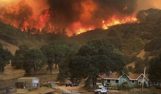 Flames from a wildfire advance down a hillside, towering over homes off Scotts Valley Road, Thursday, Aug. 2, 2018, near Lakeport, Calif. (Kent Porter /The Press Democrat via AP)