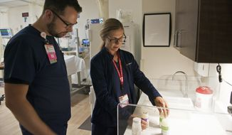 Diane Bell-Gardiner, a registered nurse at Mercy Medical Center, who lost her home in the Carr Fire, orients Christopher Smith, an RN, to the Neonatal Intensive Care Unit in Redding, Calif., Thursday, Aug. 2, 2018. Bell-Gardiner is one of more than three dozen physicians, nurses and staff at Dignity Health Mercy Medical Center in Redding without homes who are coming to work to keep the hospital running. (AP Photo/Michael Burke)