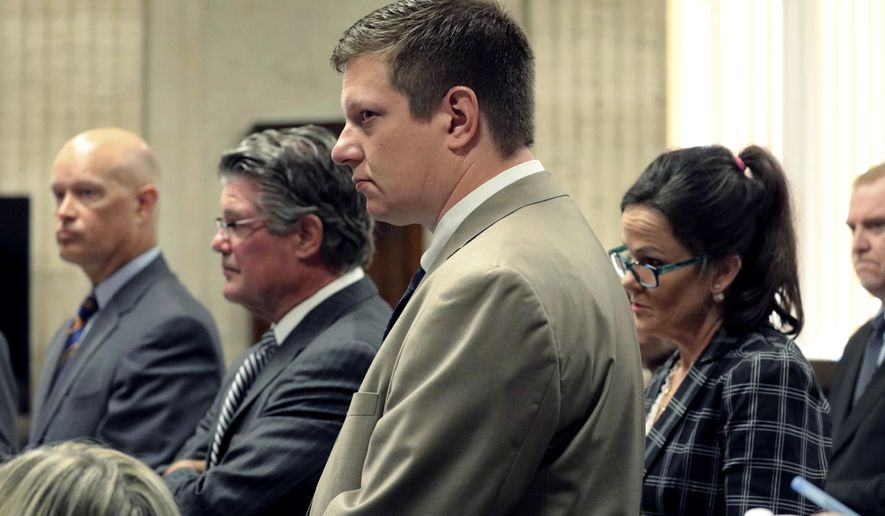 FILE - In this July 17, 2018 photo, Chicago police Officer Jason Van Dyke, center, attends a hearing at the Leighton Criminal Court Building, in Chicago. A judge overseeing the murder trial of Van Dyke in the 2014 fatal shooting of 17-year-old Laquan McDonald is holding off deciding whether the trial's location should be changed. Cook County Circuit Judge Vincent Gaughan on Friday, Aug. 3 said he will wait until jury selection to determine if a fair jury can be chosen for the trial of Van Dyke. Van Dyke's lawyers want the trial, scheduled to begin Sept. 5, moved out of Cook County. (Antonio Perez/Chicago Tribune via AP, Pool File)
