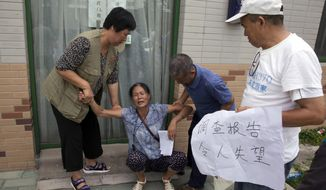 """Relatives of Chinese passengers onboard the missing Malaysia Airlines Flight 370 assist another relative near a banner which reads """"Investigation report disappoints"""" after gathering to hear the report by a 19-member international team in Beijing, China, Friday, Aug. 3, 2018. The relatives are refusing to accept the latest report on the plane's disappearance four years ago and are demanding the search be restarted. (AP Photo/Ng Han Guan)"""