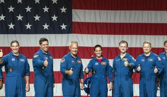 Astronauts, from left, Victor Glover, Michael Hopkins, Robert Behnken, Douglas Hurley, Nicole Mann, Christopher Ferguson, Eric Boe, Josh Cassada and Sunita Williams give a thumbs up to the crowd after NASA announced them as astronauts assigned to crew the first flight tests and missions of the Boeing CST-100 Starliner and SpaceX Crew Dragon, Friday, Aug. 3, 2018, in Houston. The astronauts will ride the first commercial capsules into orbit next year and return human launches to the U.S. (AP Photo/David J. Phillip)