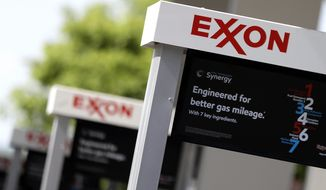 File-This April 25, 2017, file photo, shows Exxon service station signs in Nashville, Tenn. The Trump administration has dropped a two-year investigation into how Exxon Mobil Corp. factors climate-change regulations into how it calculates the value of its assets. The Securities and Exchange Commission informed the energy giant in a letter that it would not recommend an enforcement action against the company at this time. Exxon Mobil spokesman Scott Silvestri said on Friday, Aug. 3, 2018, that the company cooperated fully with the SEC inquiry. He says Exxon is confident its financial reporting meets all legal and accounting requirements. The SEC letter says its decision should not be construed as an exoneration. The agency declined further comment. (AP Photo/Mark Humphrey, File)