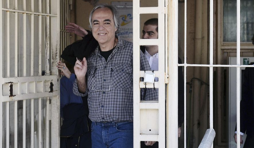 FILE - In this Thursday, Nov. 9, 2017 file photo, Dimitris Koufodinas smiles as he leaves Korydallos prison in western Athens. A convicted Greek far-left terrorist serving multiple life terms for a string of assassinations has been moved to a minimum-security prison in central Greece. Dimitris Koufodinas, 61, who has been in custody since 2002, was transferred Friday, Aug. 3, 2018 from Korydallos prison near Athens to an agricultural prison in the central town of Volos. (Yannis Kotsiaris/InTime News via AP, file)