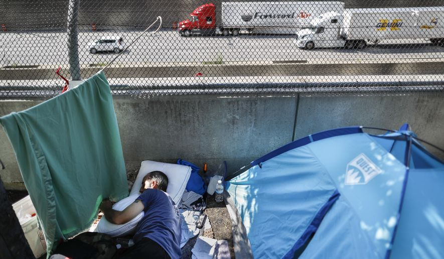 A resident of a homeless encampment along Third St. rests beside a tent after an emergency motion was filed asking a federal judge to stop Cincinnati officials from tearing down their tent city., Friday, Aug. 3, 2018, in Cincinnati. The lawsuit was filed Friday hours before city officials planned to clear a homeless encampment near a busy downtown entertainment district that includes stadiums where the Cincinnati Reds and Bengals play. Crews handed out 72-hour notices to people living at the camp Tuesday. (AP Photo/John Minchillo)