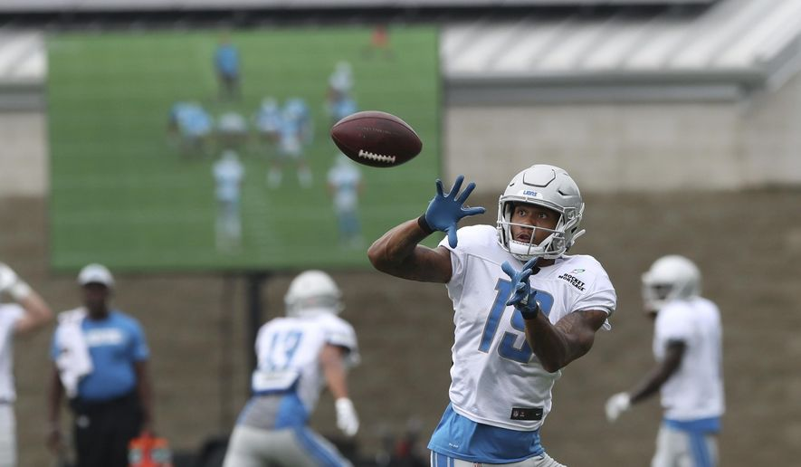 In a photo from Aug. 1, 2018, Detroit Lions receiver Kenny Golladay makes a catch in front of a monitor displaying a play in the background during NFL football practice in Allen Park, Mich. The Lions are among the teams in the league making instant replay available to make quick corrections and observations. (AP Photo/Carlos Osorio)