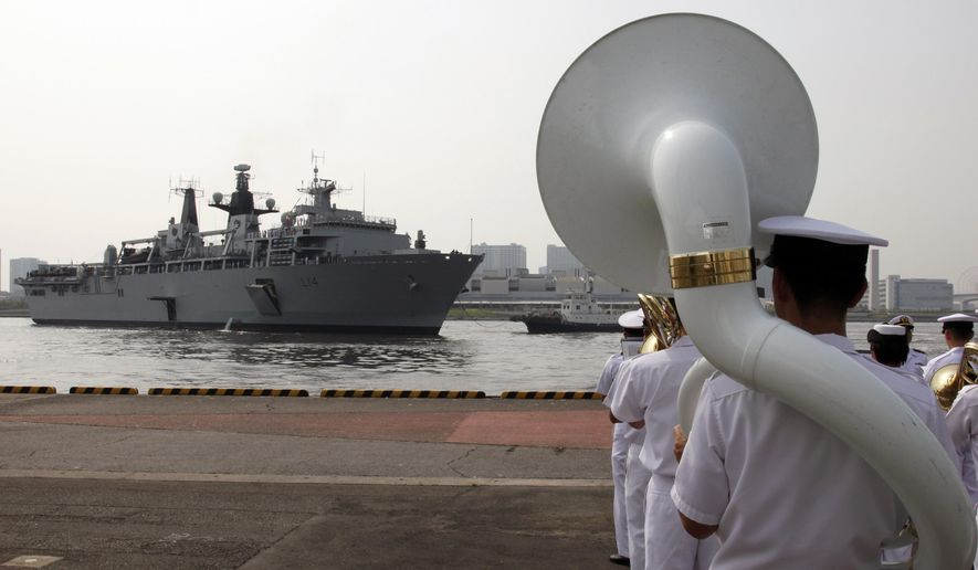 Japan Self-Defense Forces marching band members perform as British Royal Navy's HMS Albion amphibious assault ship arrives at a dock in Tokyo Friday, Aug. 3, 2018. The British warship has docked in Tokyo as Britain seeks to expand its military presence in the Asia-Pacific region. (AP Photo/Ken Moritsugu)