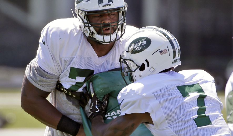 FILE - In this Wednesday, Aug. 1, 2018 file photo,New York Jets' Darius James, left, works with Tre McBride during practice at the NFL football team's training camp in Florham Park, N.J. Darius James was pretty sure he was OK, even though he couldn't turn his neck. He wiggled his fingers and toes and had feeling in his arms and legs, giving the big offensive lineman some reassurance that he wasn't paralyzed. But his neck wouldn't budge. (AP Photo/Seth Wenig, File)