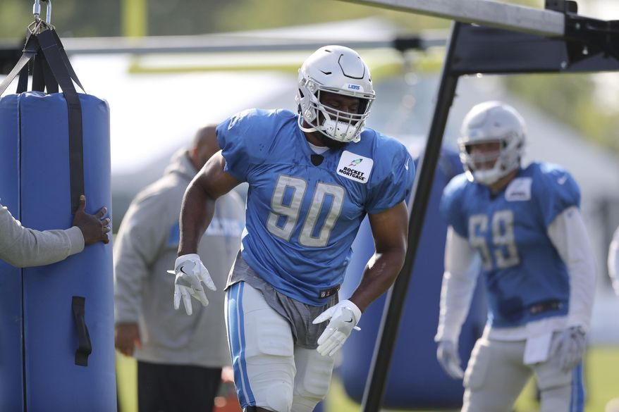 Detroit Lions defensive end Cornelius Washington walks off after hitting a blocking dummy during NFL football practice, Friday, Aug. 3, 2018, in Allen Park, Mich. Washington has returned to practice. Detroit removed Washington from the injured reserve/non-football injury list on Friday. He had 2 1/2 sacks in 15 games with the Lions last season, his fifth in the NFL. (AP Photo/Carlos Osorio)