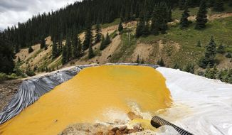 FILE - In this Aug. 12, 2015, file photo, wastewater flows through a retention pond built to contain and remove heavy metals from the Gold King Mine outside Silverton, Colo. The U.S. Environmental Protection Agency accidentally triggered a spill of 3 million gallons of wastewater from the mine. The Obama administration said it could not legally repay any of the claims for damage from the spill, but the Trump administration promised last year to reconsider. As of Friday, Aug. 3, 2018, no claims had been paid, but the agency said it is continuing to review them. (AP Photo/Brennan Linsley, fie)