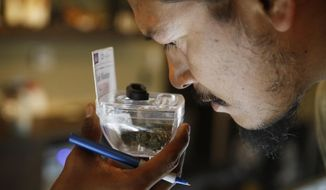 In this July 30, 2018, photo, Paul Whiterock smells marijuana for sale at 420 Sahara Wellness in Las Vegas. Nevada regulators and industry insiders say the state's first year of adult-use marijuana sales has exceeded their expectations. (AP Photo/John Locher)