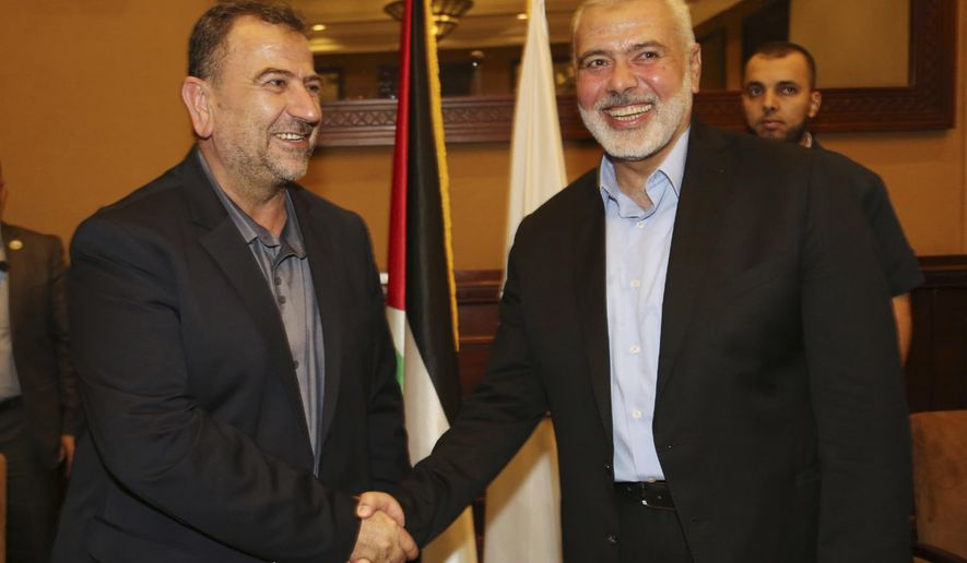 In this photo released by the Hamas Media Office, Ismail Haniyeh, right, the head of the Hamas political bureau, shakes hands with his deputy Saleh Arouri upon his arrival in Gaza from Cairo, Egypt, in Gaza City, Thursday, Aug. 2, 2018. Egypt is trying to broker a broad cease-fire deal between Israel and Gaza's Hamas rulers that is to pave the way for Gaza's reconstruction and an eventual prisoner swap, senior Hamas officials said Thursday. Repeated cease-fire deals over the years collapsed, but there were signs of possible momentum toward a new agreement, after weeks of escalation along the Gaza-Israel frontier. (Mohammad Austaz/Hamas Media Office via AP)