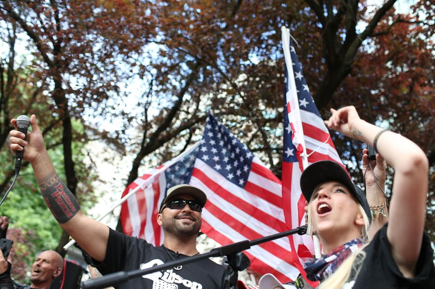 In this June 30, 2018, file photo, Joey Gibson, left, leader of Patriot Prayer, heads the group's rally in Portland, Ore. Portland is bracing for what could be another round of violent clashes Saturday, Aug. 4, 2018, between a right-wing group holding a rally here and self-described anti-fascist counter-protesters who have pledged to keep Patriot Prayer and other affiliated groups out of this ultra-liberal city. (Mark Graves/The Oregonian via AP, file)
