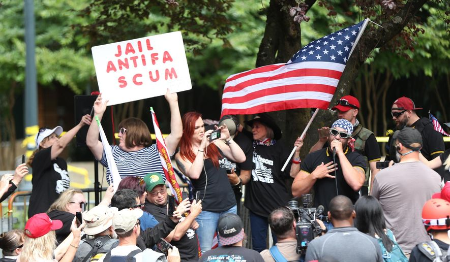 FILE--In this June 30, 2018, file photo, the Patriot Prayer group holds a rally and march in Portland, Ore., amid a protest by anti-fascist groups. Portland is bracing for what could be another round of violent clashes Saturday, Aug. 4, 2018, between a right-wing group holding a rally here and self-described anti-fascist counter-protesters who have pledged to keep Patriot Prayer and other affiliated groups out of this ultra-liberal city. (Mark Graves/The Oregonian via AP, file)