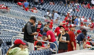 Fans stand after it was announced that the baseball game between the Washington Nationals and the Cincinnati Reds was postponed at Nationals Park, Friday, Aug. 3, 2018, in Washington. The game is rescheduled for Saturday, Aug. 4th. (AP Photo/Alex Brandon)