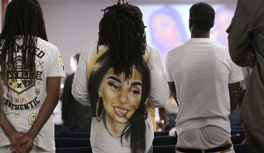 People stand during the funeral for 18-year-old Nia Wilson, who was stabbed to death at a train station, in Oakland, Calif., Friday Aug. 3, 2018. Wilson was stabbed to death July 22 on a Bay Area Rapid Transit platform in an unprovoked attack against her and her sister. People remembered Wilson's loving nature, her musical talents and her aspirations to become a paramedic or join the military. (AP Photo/Lorin Eleni Gill)