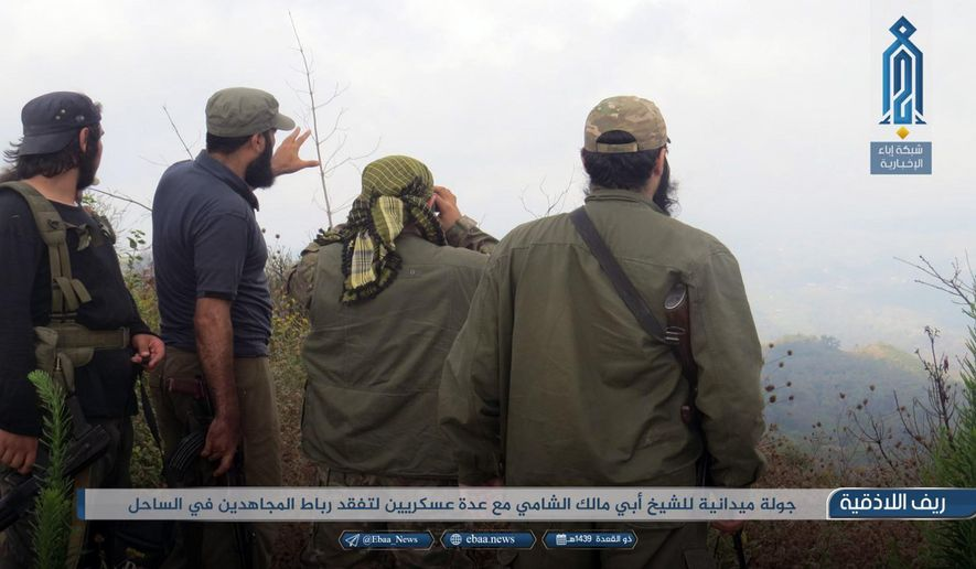 "This photo provided on Monday, July 22, 2018, by the al-Qaida-affiliated Ibaa News Network, purports to show militants of the al-Qaida-linked coalition known as Hay'at Tahrir al-Sham, Hay'at Tahrir al-Sham, Arabic for Levant Liberation Committee overlooking a battlefield in rural Lattakia, Syria. It's already being called the ""mother of all battles,"" the last showdown between the forces of Syrian President Bashar Assad and the opposition. Idlib province, in Syria's northwest, is the only significant opposition enclave still standing and Assad has vowed to retake it. The caption in Arabic reads: ""A field visit by Sheik Abu Malik al-Shami (a leading member of the group) with field commanders to inspect an outpost for Mujahideen (holy fighters) in the coast area."" (Ibaa News Network, via AP)"