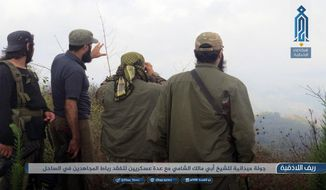 """This photo provided on Monday, July 22, 2018, by the al-Qaida-affiliated Ibaa News Network, purports to show militants of the al-Qaida-linked coalition known as Hay'at Tahrir al-Sham, Hay'at Tahrir al-Sham, Arabic for Levant Liberation Committee overlooking a battlefield in rural Lattakia, Syria. It's already being called the """"mother of all battles,"""" the last showdown between the forces of Syrian President Bashar Assad and the opposition. Idlib province, in Syria's northwest, is the only significant opposition enclave still standing and Assad has vowed to retake it. The caption in Arabic reads: """"A field visit by Sheik Abu Malik al-Shami (a leading member of the group) with field commanders to inspect an outpost for Mujahideen (holy fighters) in the coast area."""" (Ibaa News Network, via AP)"""