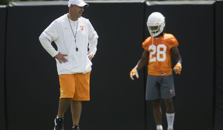 Tennessee head coach Jeremy Pruitt, left, stands on the field during the first NCAA college football practice of the season in Knoxville, Tenn., Friday, Aug. 3, 2018. (Caitie McMekin/Knoxville News Sentinel via AP)