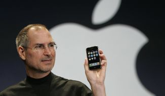 FILE - In this Jan. 9, 2007 file photo, Apple CEO Steve Jobs holds up the new iPhone during his keynote address at MacWorld Conference & Expo in San Francisco.  Apple has become the world's first company to be valued at $1 trillion, the financial fruit of tasteful technology that has redefined society since two mavericks named Steve started the company 42 years ago.  (AP Photo/Paul Sakuma, File)