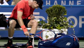 Andy Murray, of Britain, hits his bag after losing the first set of a match against Marius Copil, of Romania, during the Citi Open tennis tournament in Washington, Friday, Aug. 3, 2018. (AP Photo/Andrew Harnik)