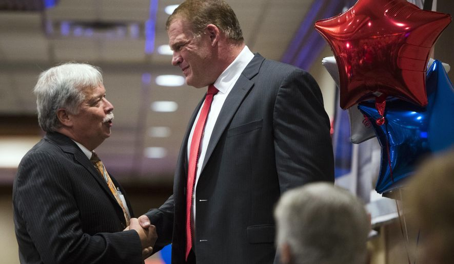 GOP chair Buddy Burkhardt, left, shakes the hand of Glenn Jacobs after early results showed Jacobs winning the mayoral race, Thursday, Aug. 2, 2018, in Knoxville, Tenn. Republican Jacobs, who is also the WWE wrestler known as Kane, defeated Democrat Linda Haney. (Caitie McMekin/Knoxville News Sentinel via AP)