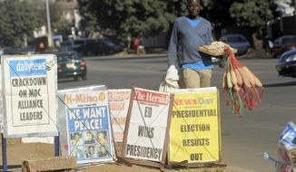 A vendor sells sponges near newspaper headlines on the streets of Harare, Friday, Aug. 3, 2018. Zimbabwe's President Emmerson Mnangagwa won an election Friday with just over 50 percent of the ballots as the ruling party maintained control of the government in the first vote since the fall of longtime leader Robert Mugabe (AP Photo/Tsvangirayi Mukwazhi)