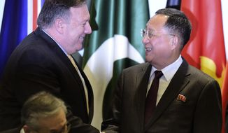 U.S. Secretary of State Mike Pompeo, left, greets North Korea's Foreign Minister Ri Yong Ho as they prepare to pose for a group photograph at the 25th ASEAN Regional Forum Retreat in Singapore, Saturday, Aug. 4, 2018. (AP Photo/Joseph Nair)