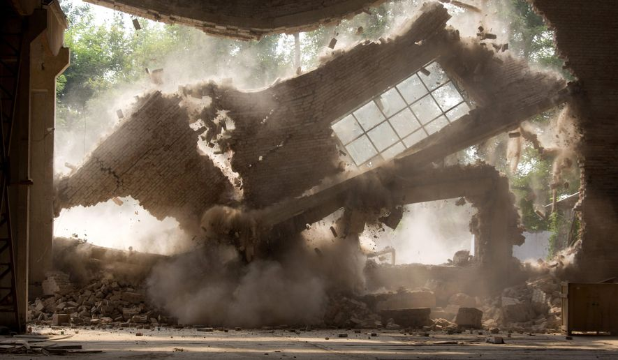 """Walls of Chinese artist Ai Weiwei's studio collapse during demolition in Beijing Saturday, Aug. 4, 2018. The frequent government critic says on his Instagram account the demolition began Friday without prior notice and posted videos of an excavator smashing the windows of his """"Zuoyou"""" studio. (AP Photo/Ng Han Guan)"""