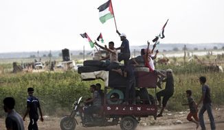 Men wave national flags while riding a motorcycle-taxi, called a Toktok, loaded with tires to be burned during a protest at the Gaza Strip's border with Israel, Friday, Aug. 3, 2018. Gaza's Hamas rulers led several thousand Palestinians in a protest along the frontier with Israel on Friday _ a show of presence by Hamas as Egyptian efforts intensify to broker a broad truce between the Islamic militant group and Israel. (AP Photo/Khalil Hamra)