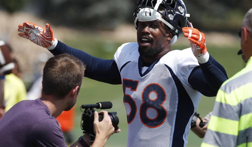 Denver Broncos linebacker Von Miller leads fans in singing birthday wishes to a fan as Miller works the rope line after drills at the team's headquarters during an NFL football training camp Saturday, Aug. 4, 2018, in Englewood, Colo. (AP Photo/David Zalubowski)