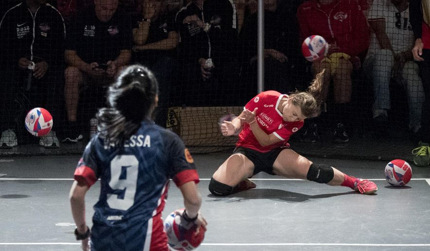 An Austria player, right, is hit by the ball during women's competition against Malaysia in the Dodgeball World Cup, Saturday, Aug. 4, 2018, in New York. (AP Photo/Mary Altaffer)