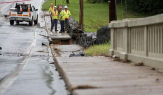 Workers from the City of Lynchburg and Wiley Wilson inspect College Lake Dam on Friday, Aug. 3, 2018 in Lynchburg, Va. Around 130 residents downstream of College Lake were evacuated the night before after a deluge on rain hit the area causing a fear of the dam failing. (AP Photo/Jill Nance)