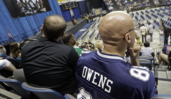 Reyad Rasul, of Columbus, Ohio, right, wears a Terrell Owens jersey as he waits for the former wide receiver to deliver his NFL Pro Football Hall of Fame speech on Saturday, Aug. 4, 2018, in Chattanooga, Tenn. Rasul was planning on going to Canton, Ohio, to see the Hall of Fame festivities in person, but changed his plans when Owens decided to celebrate his induction at the University of Tennessee at Chattanooga, where he played football and basketball and ran track. (AP Photo/Mark Humphrey)