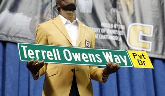 Former wide receiver Terrell Owens holds a street sign after a road was named for him following his Pro Football Hall of Fame speech, Saturday, Aug. 4, 2018, in Chattanooga, Tenn. Instead of speaking at the Hall of Fame events in Canton, Ohio, Owens celebrated his induction at the University of Tennessee at Chattanooga, where he played football and basketball and ran track. (AP Photo/Mark Humphrey)