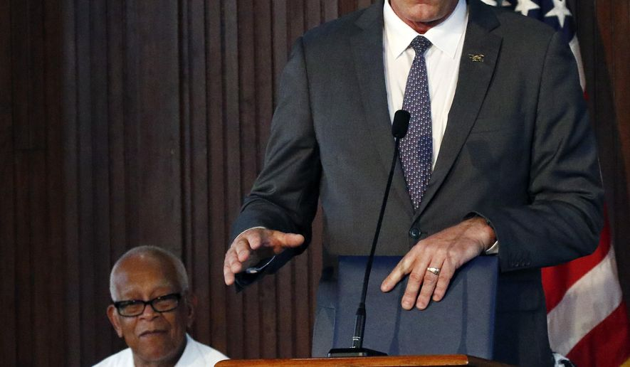 Hollis Watkins, chairman of the Veterans of the Mississippi Civil Rights Movement, seated, listens as Interior Secretary Ryan Zinke, speaks of the importance of signing a proclamation designating the former home of the late civil rights activist Medgar Evers and his widow Myrlie Evers, into the African American Civil Rights Network, Friday, Aug. 3, 2018, at Tougaloo College in Jackson, Miss. Evers was the Mississippi NAACP's first field secretary beginning in 1954 and was assassinated at the house in 1963. (AP Photo/Rogelio V. Solis)