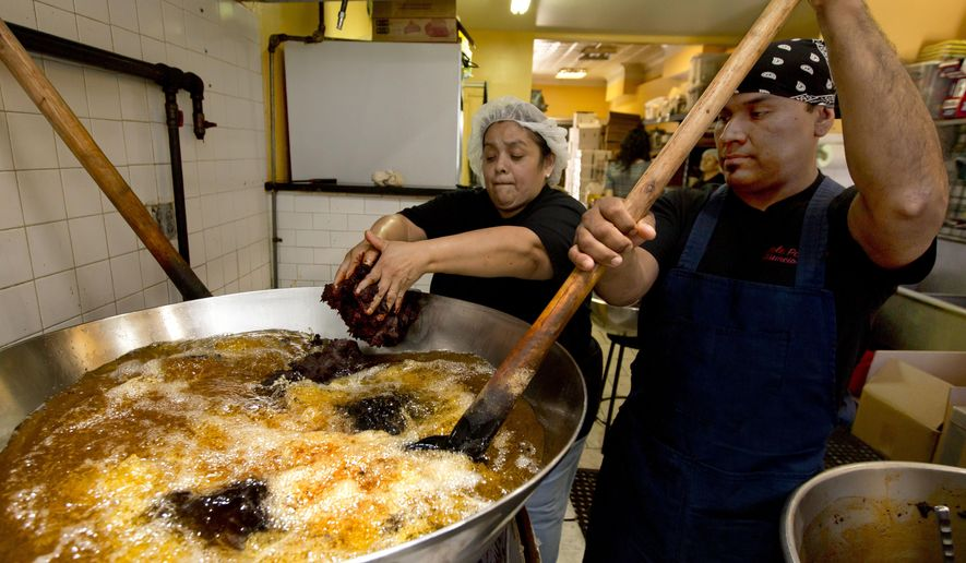 Christina Mora and Franco Hernandez start a new batch of mole at the headquarters of Mole Poblano Asuncion Corp., in the Bushwick neighborhood of Brooklyn borough of New York, Tuesday, July 31, 2018. This family-run business, that produces about 1,600 pounds of mole a day in a small Brooklyn store, has grown due to the three generations of a matriarchy that produce the dark-hued paste of ground chilies and a dozen other ingredients. (AP Photo/Richard Drew)