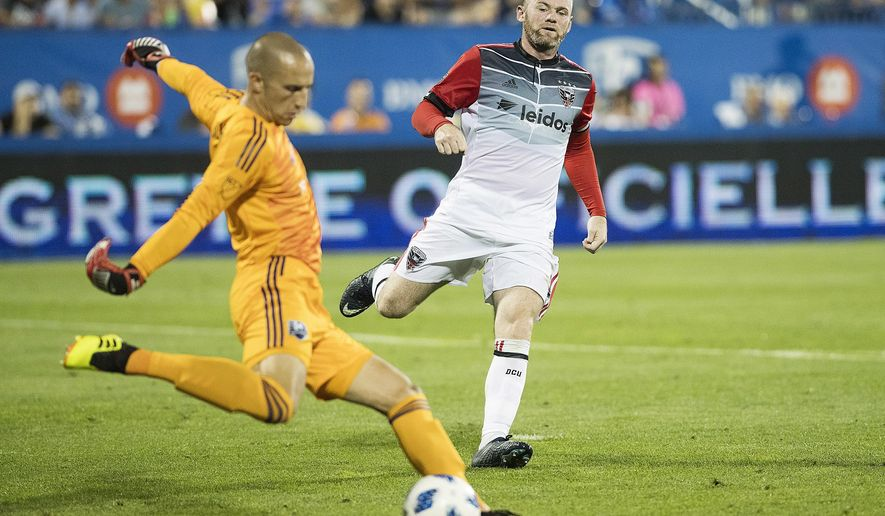 D.C. United's Wayne Rooney, right, pressures Montreal Impact goalkeeper Evan Bush during the second half of an MLS soccer match Saturday, Aug. 4, 2018, in Montreal. (Graham Hughes/The Canadian Press via AP)