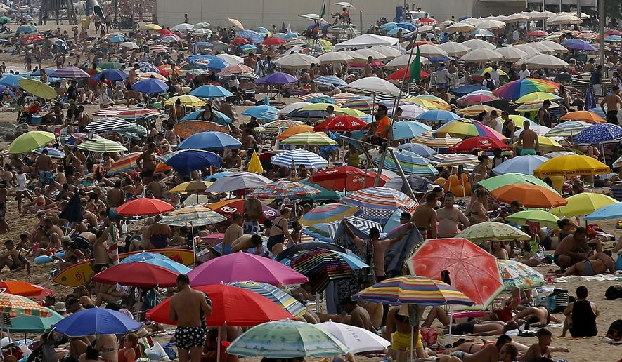 People sunbathe on a beach during a hot summer day in Barcelona, Spain, Saturday, Aug. 4, 2018. Hot air from Africa is bringing a heat wave to Europe, prompting health warnings about Sahara Desert dust and exceptionally high temperatures that could peak at 47 degrees Celsius (117 Fahrenheit) in Spain and Portugal. (AP Photo/Manu Fernandez)