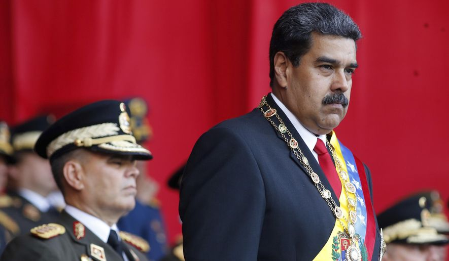 In this  May 24, 2018, file photo, Venezuela's President Nicolas Maduro watches a military parade, alongside his Defense Minister Vladimir Padrino Lopez, behind, at Fort Tiuna in Caracas, Venezuela. State television in Venezuela showed President Maduro abruptly cutting short a speech on Saturday, Aug. 4, causing hundreds of soldiers present to break ranks and scatter.(AP Photo/Ariana Cubillos, File)