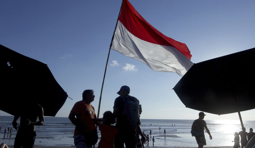 Tourists stand under the national flag on a beach during the sunset in Bali, Indonesia, Tuesday, Aug. 8, 2017. (AP Photo/Firdia Lisnawati)