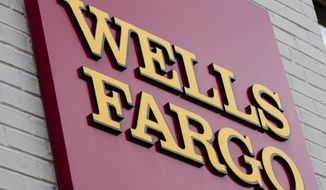 FILE - This Friday, Aug. 11, 2017, file photo shows a sign at a Wells Fargo bank location in Philadelphia. On Friday, Jan. 12, 2018, Wells Fargo said its fourth-quarter earnings rose 17 percent from a year earlier, as the consumer banking giant benefited from the recently passed GOP tax bill, but incurred additional costs related to improper sales practices and other matters. (AP Photo/Matt Rourke, File)