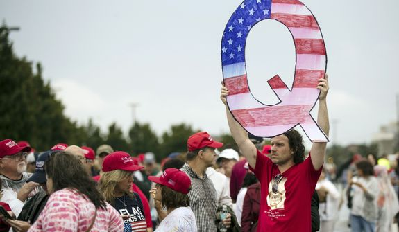 David Reinert displayed a Q sign at a Pennsylvania campaign rally Thursday with President Trump and Senate candidate Lou Barletta. (Associated Press)