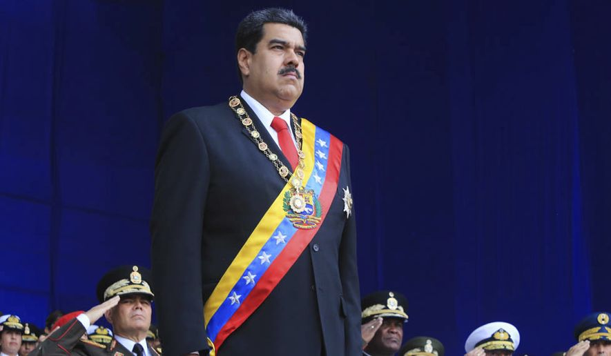 In this photo provided by the Miraflores Presidential Palace, President Nicolas Maduro stands at attention during a event marking the 81st anniversary of the National Guard, in Caracas, Venezuela, Saturday, August 4, 2019. Venezuela's government says several explosions heard at a military event were an attempted attack on President Maduro. Information Minister Jorge Rodriguez said in a live broadcast that several drone-like devices with explosives detonated near the president. He said Maduro is safe and unharmed but that seven people were injured. (Miraflores Presidential Palace via AP)