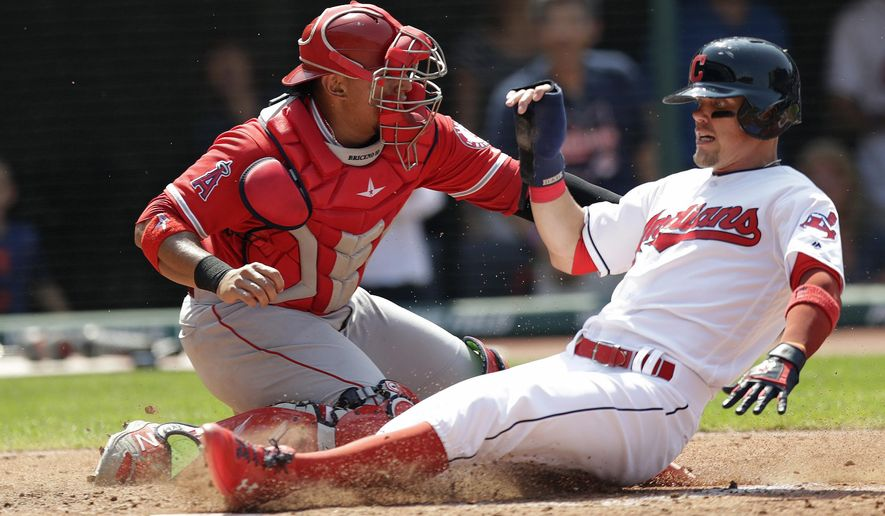 Cleveland Indians' Brandon Guyer, right, slides safely into home plate as Los Angeles Angels' Jose Briceno, left, cannot make the tag in the sixth inning of a baseball game, Sunday, Aug. 5, 2018, in Cleveland. (AP Photo/Tony Dejak)