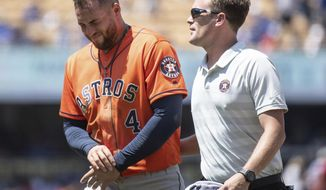 Houston Astros' George Springer, left, exits with a trainer after getting injured whiletrying to steal second base during the third inning of a baseball game against the Los Angeles Dodgers in Los Angeles, Sunday, Aug. 5, 2018. (AP Photo/Kyusung Gong)